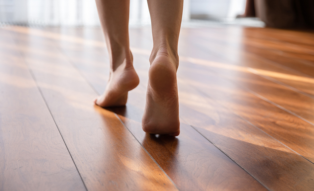 A person walks across a laminate floor on the balls of their bare feet.