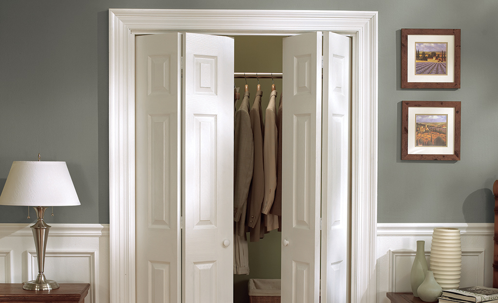 Bifold doors open slightly to show clothes hanging on a rod in a closet.