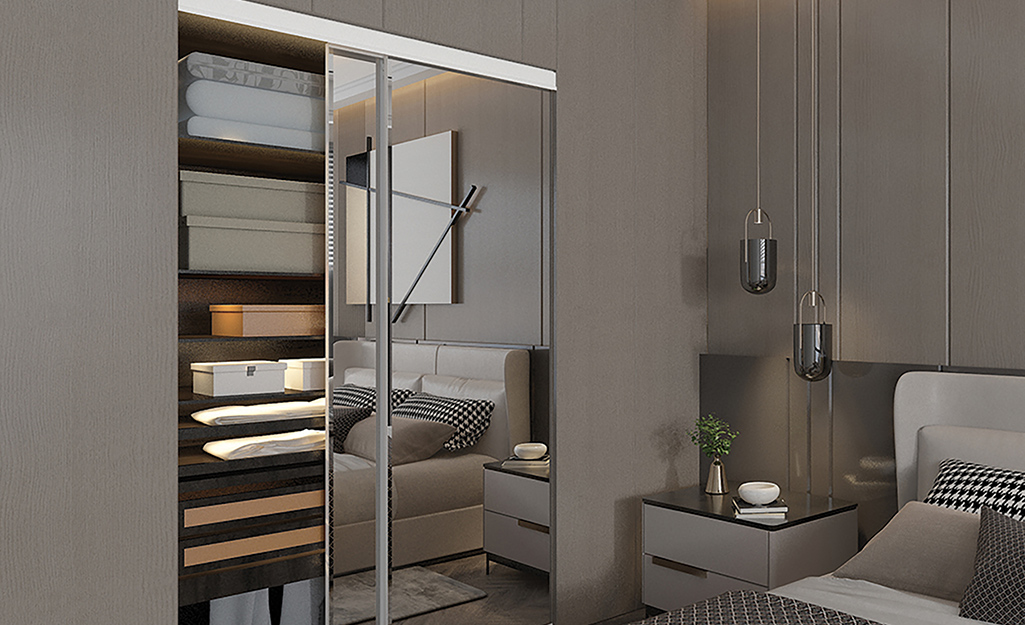 A sliding mirrored door opens to show a bedroom closet with shelves.