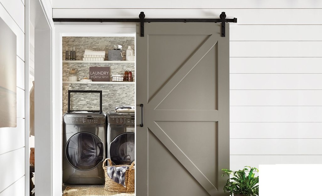 A barn door opens in front of a laundry closet with a front-loading washer and dryer.