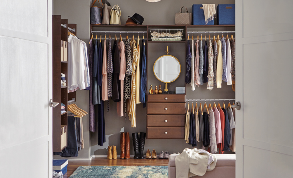 French doors open into a walk-in closet with clothing rods, drawers and shelves.