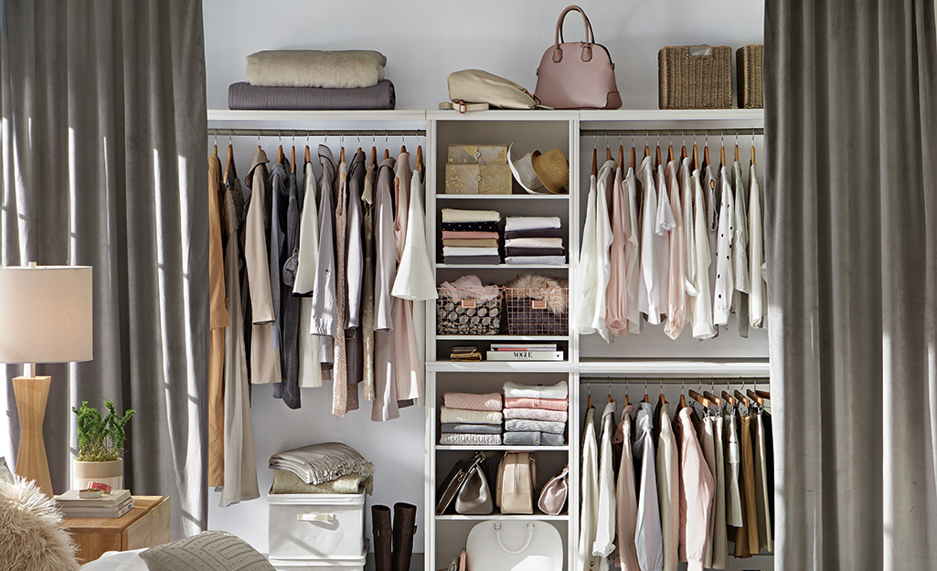 Curtains used instead of a closet door are open to show clothes hanging from rods and folded on shelves.