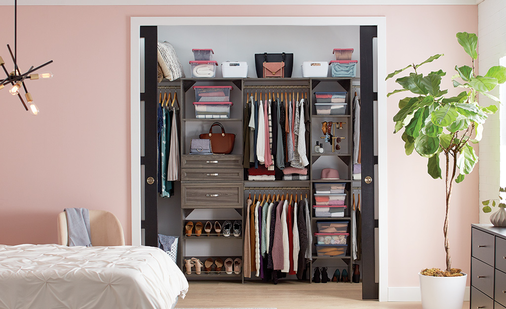 A bedroom closet with a wood closet shelving system.