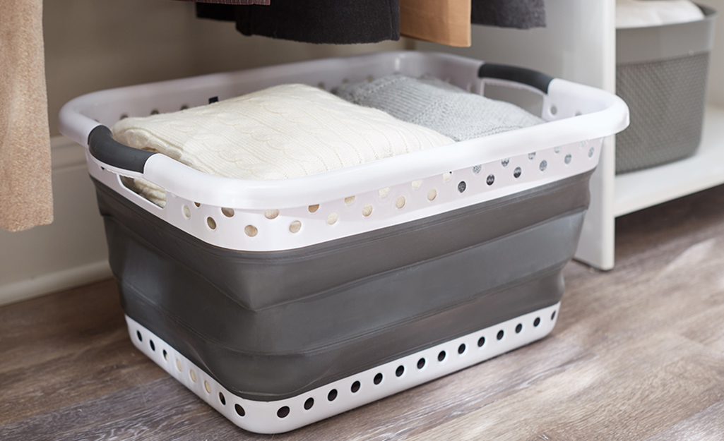 A collapsible storage bin with miscellaneous linens inside.