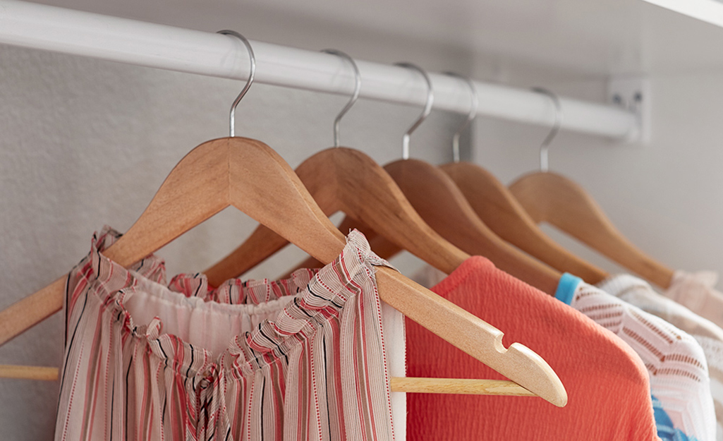 Clothes hanging from matching wood hangers on a closet hanging rod.