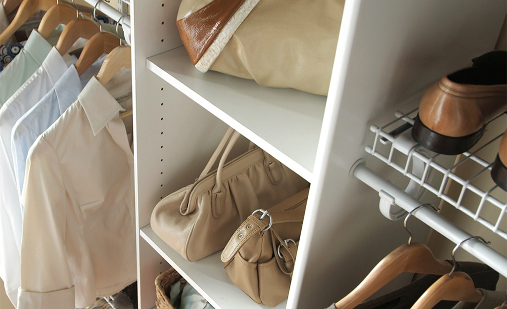 Clothes, bags, shoes and accessories neatly stored in an adjustable closet shelving system.