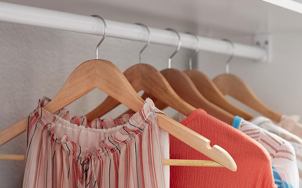 a closeup of clothes hanging in a closet