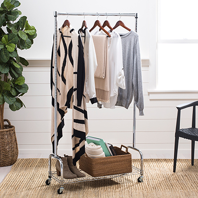 A rolling garment rack clothes on hangers and shoes on a shelf stands in a living room.