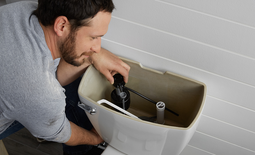 A person removes a toilet fill valve from a toilet tank.