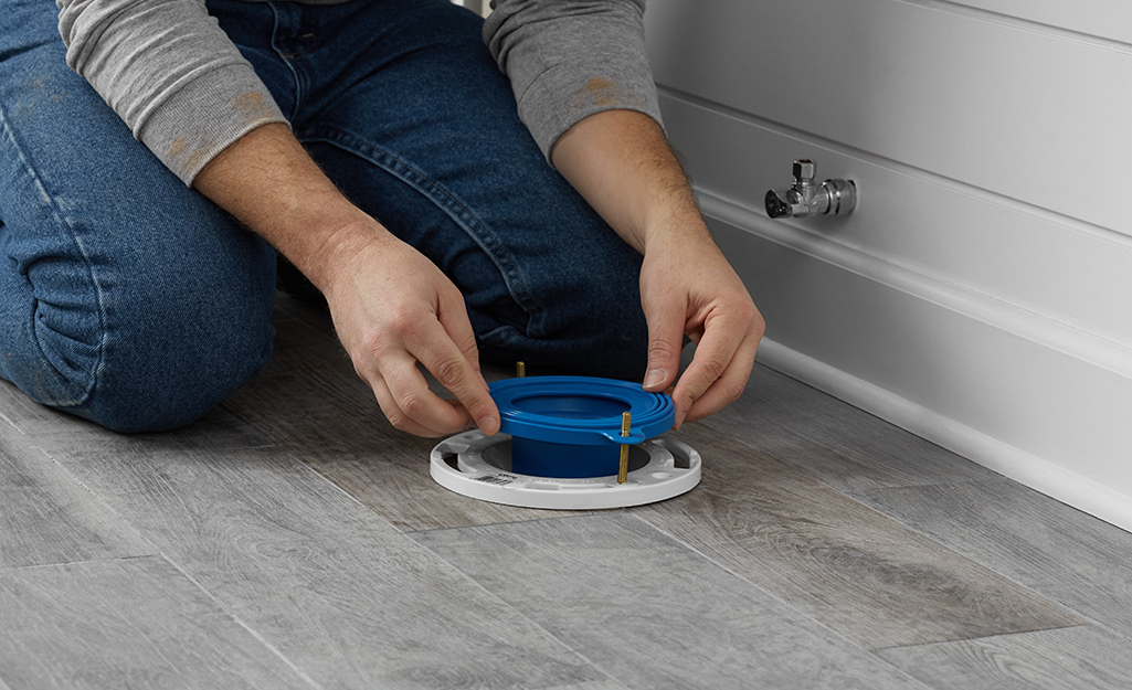 A person installs a toilet flange on the bathroom floor.