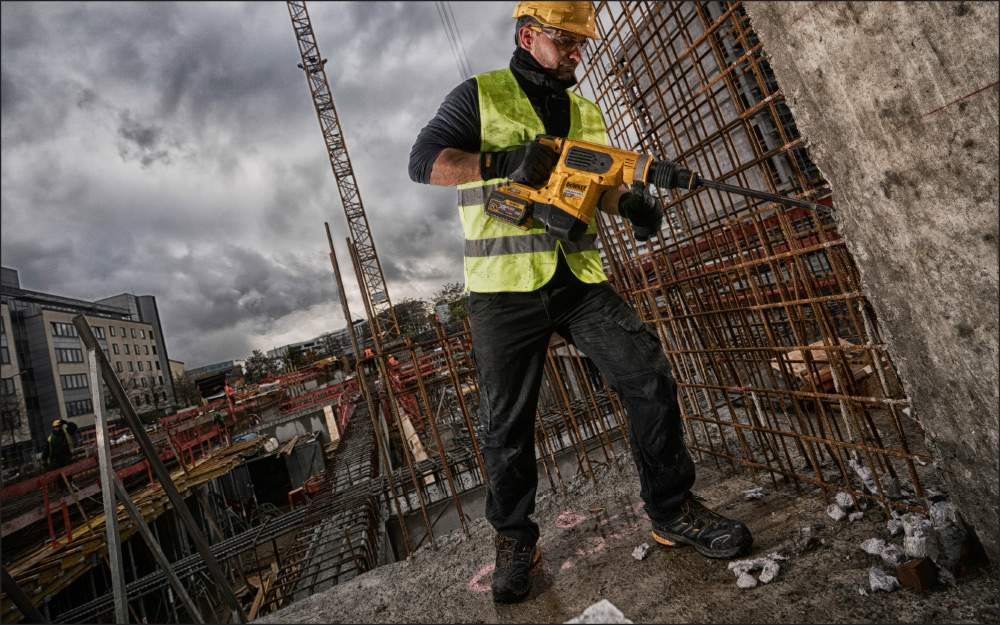 A construction worker using a hammer drill while wearing safety toe bits.