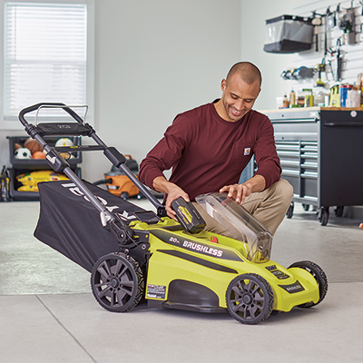 A person pushing a cordless lawn mower.