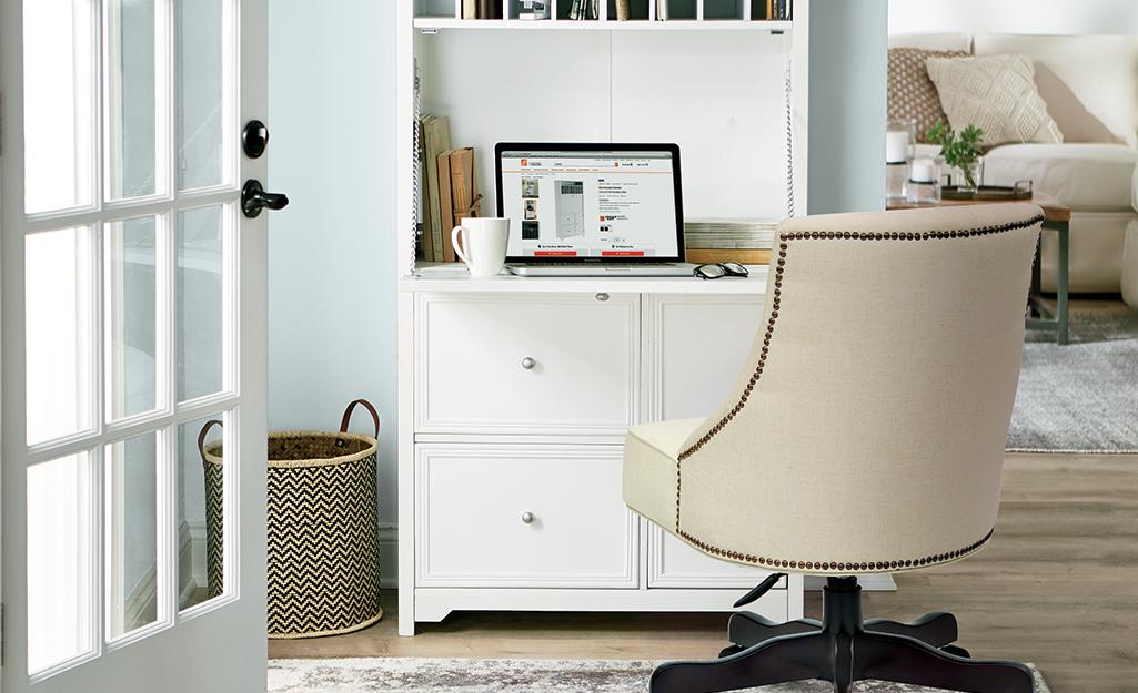 Ghế văn phòng bọc nệm đặt phía trước bàn lật xuống cạnh cửa kiểu Pháp mở.