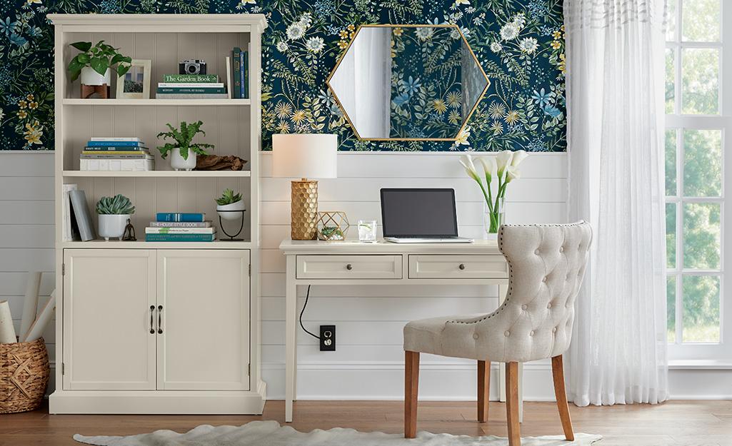 Bàn văn phòng nhỏ và tủ sách đặt trước phông nền hoa màu xanh.