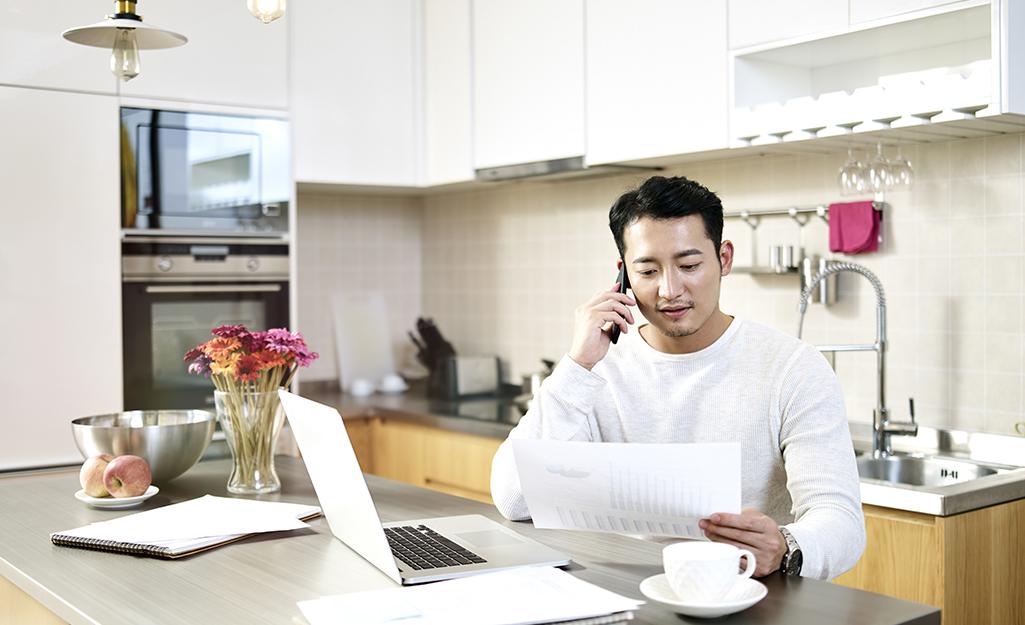 Người đàn ông làm việc tại quầy bếp với máy tính xách tay và tập tin.