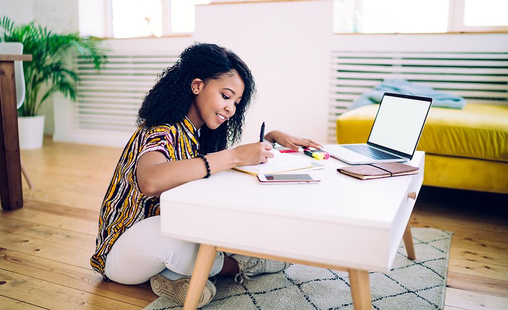 Người phụ nữ sử dụng một chiếc ghế dài làm bàn làm việc trong phòng khách của mình.