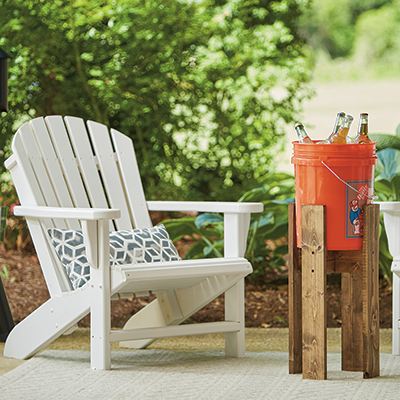 A Homer bucket being used as a cooler beside a white patio chair.