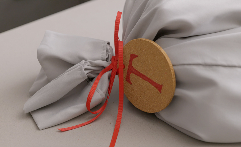 A pillowcase is tied shut with a red ribbon and coaster gift tag.