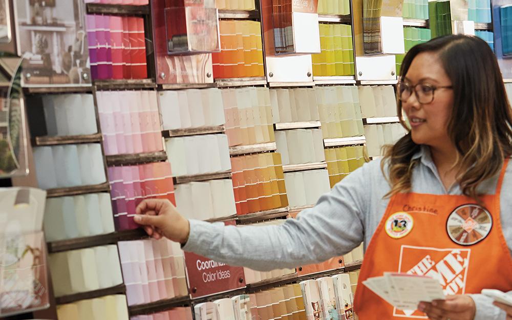 Một nhân viên Home Depot đứng bên một màn hình hiển thị các chip màu sơn.