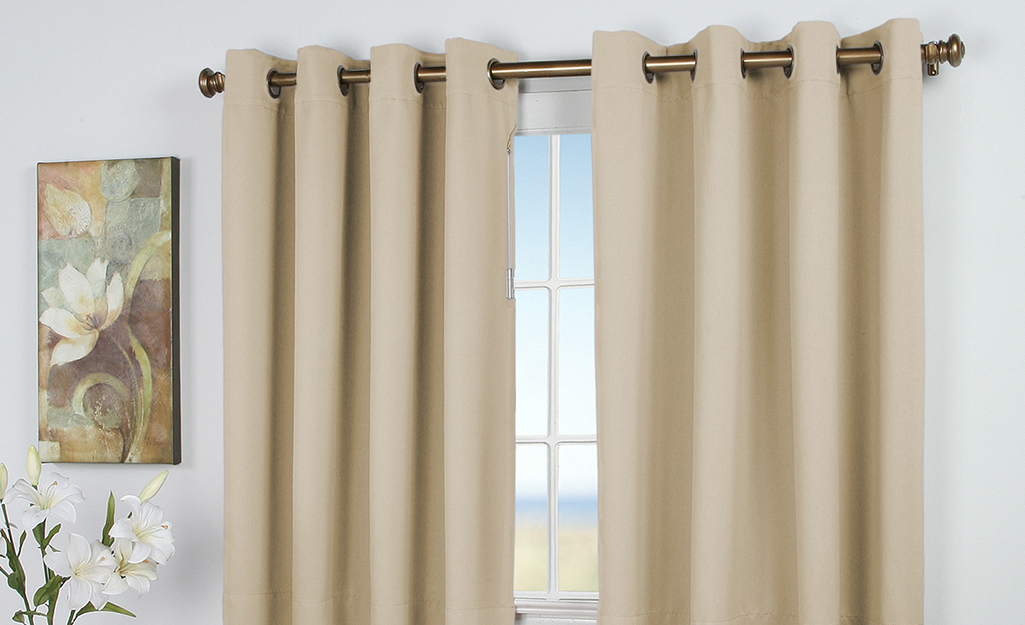 Beige grommet curtains over a window.