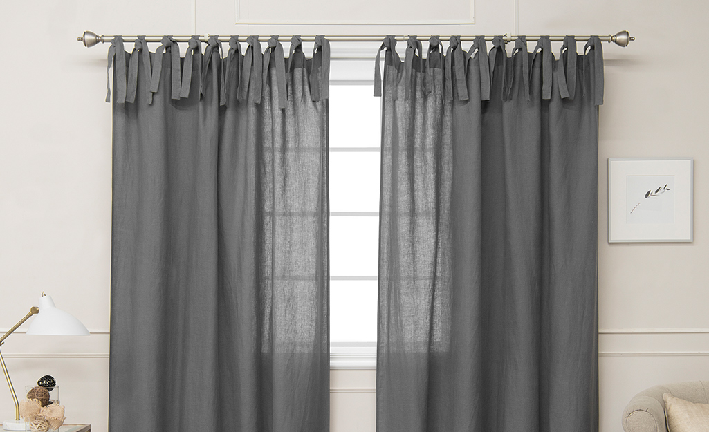 Gray tie top curtains over a window.