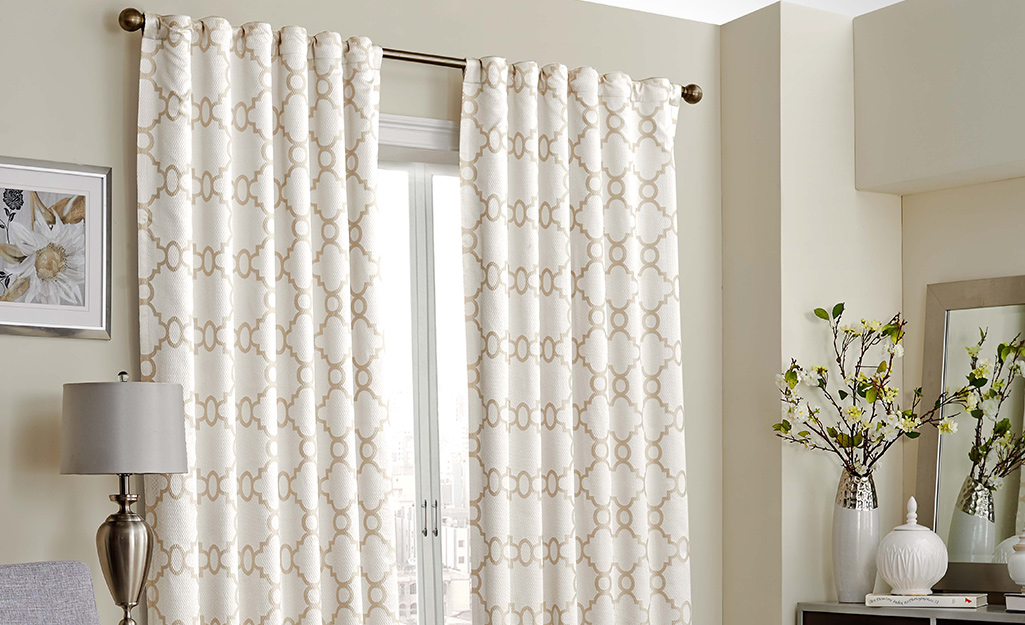 White and gold rod pocket curtains over a window.