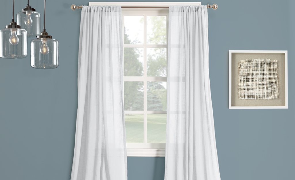 White, easy-care curtains over a dining room window.