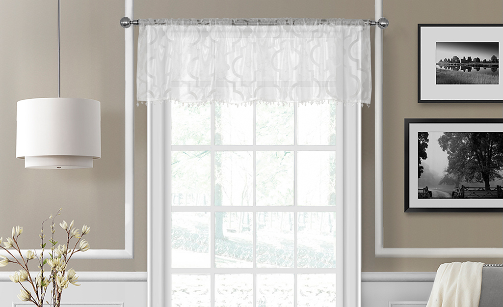 A lacy, white valance over a window.