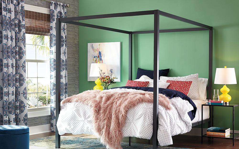 Một phòng ngủ với rèm hoa văn treo trên cửa sổ.
