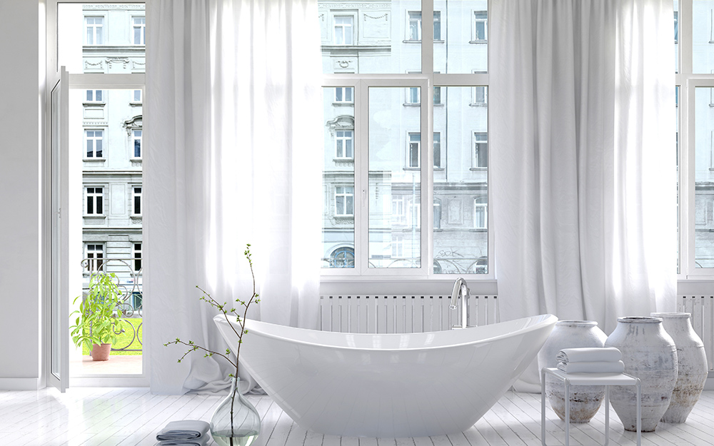 A bathroom with white curtains hanging over the windows.