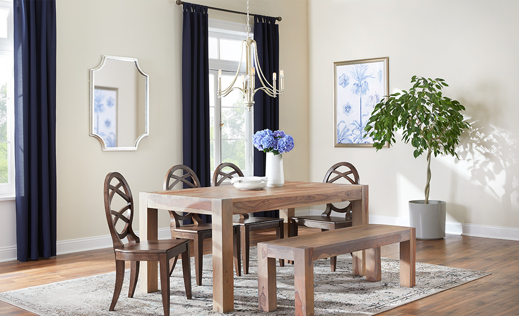 Solid color curtains hanging over windows in a dining room.