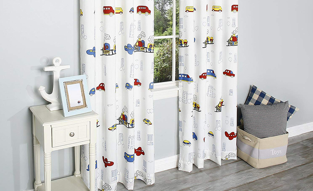 White curtains with multi-colored cars on them in a child's room.
