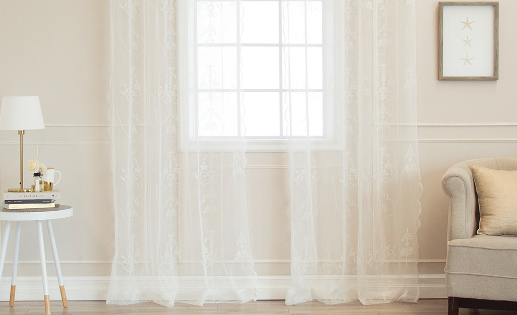 Sheer, white curtains over a living room window.