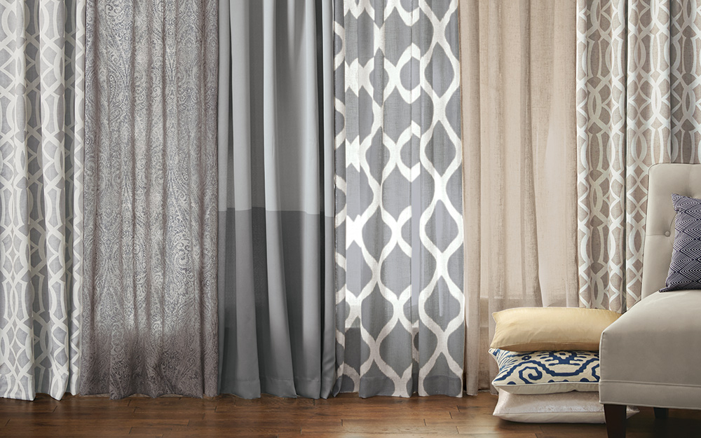 Different curtains styles hanging side by side in an empty room