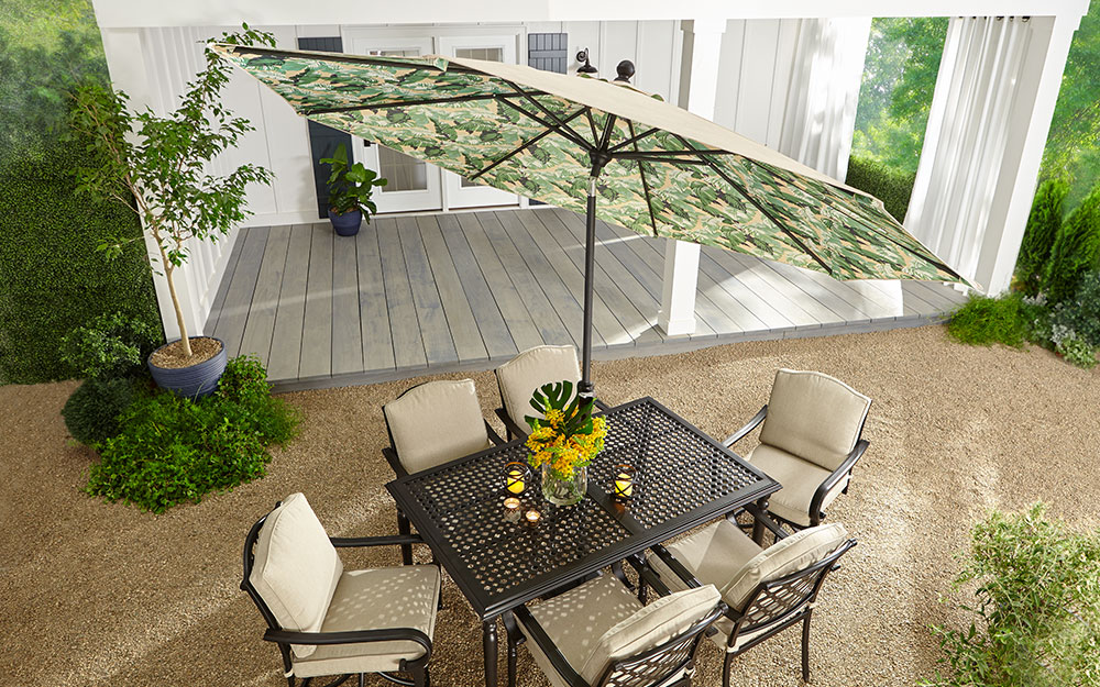 A tilted market umbrella shading an outdoor patio dining set.