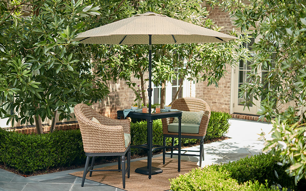 A patio umbrella shading an outdoor table and chairs.