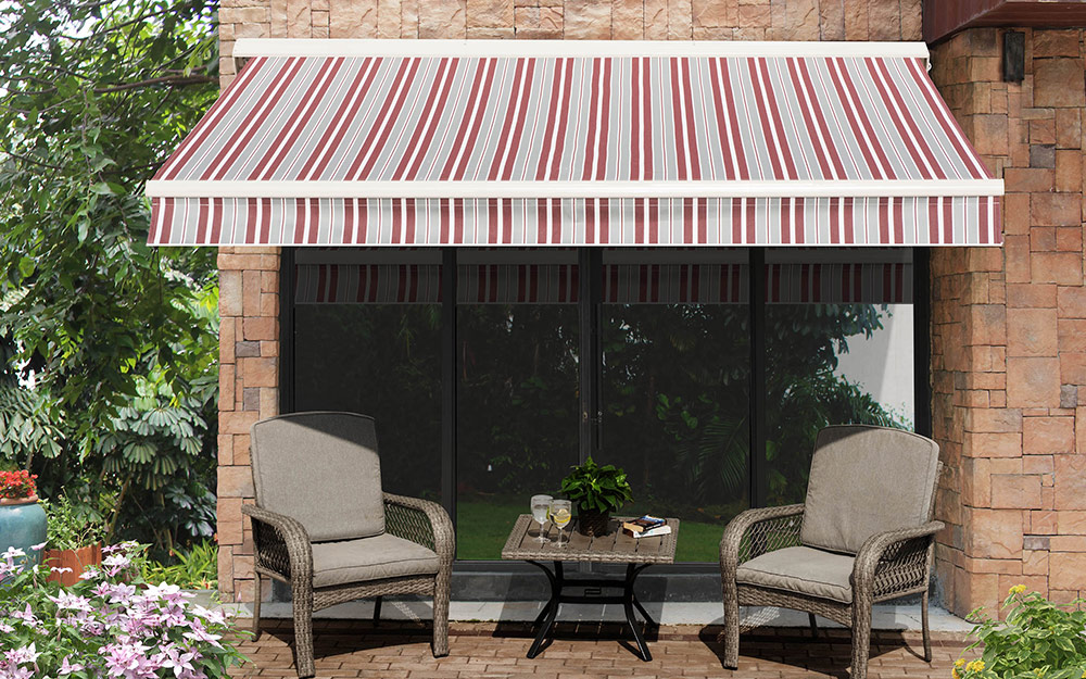 An outdoor awning providing shade over a patio table and chairs.