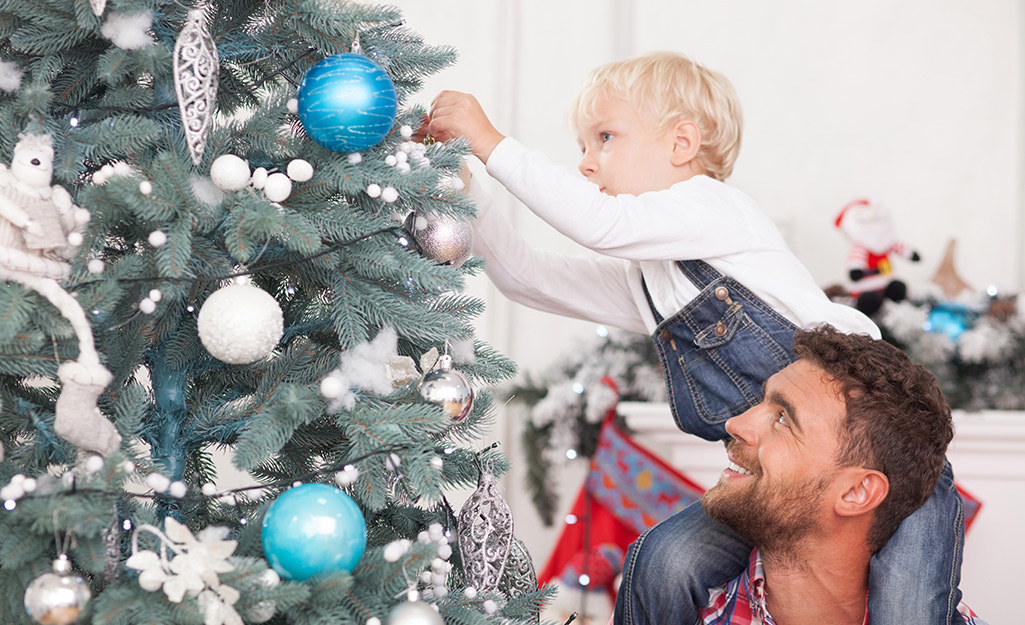 A man holding a little boy on his shoulders while the child hangs an ornament on a Christmas tree.