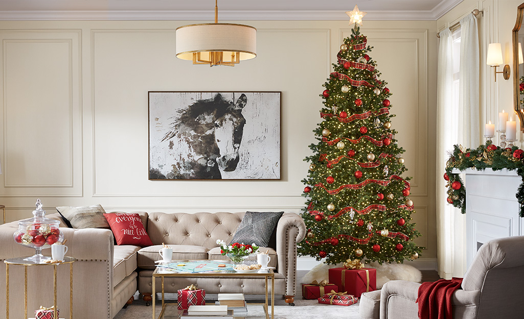 A Christmas tree decorated with ornaments, lights and ribbon in a living room.