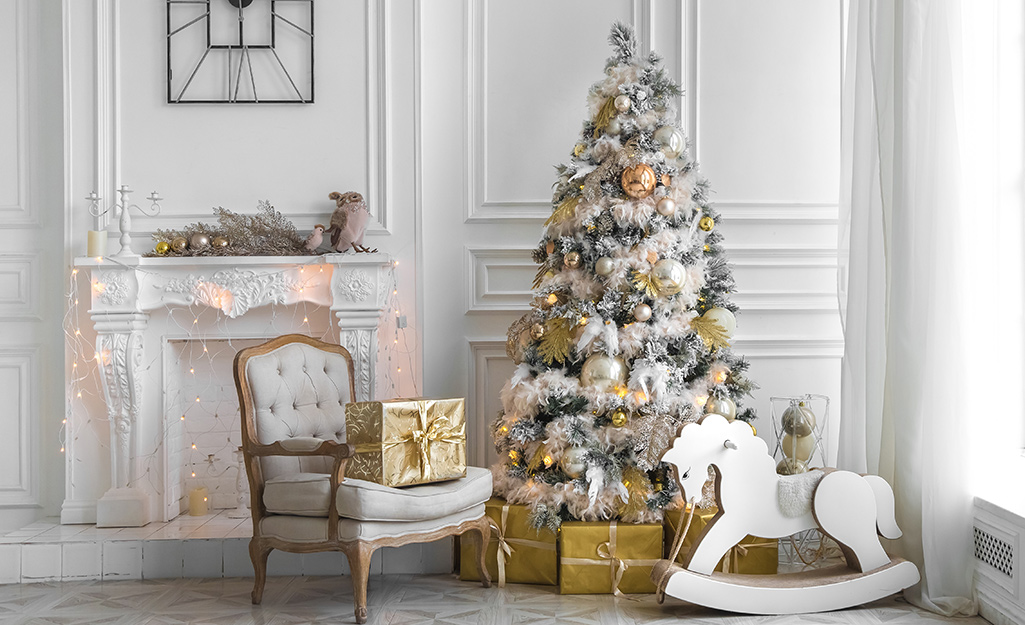 A Christmas tree decorated with white garland and gold ornaments in an all-white living room.