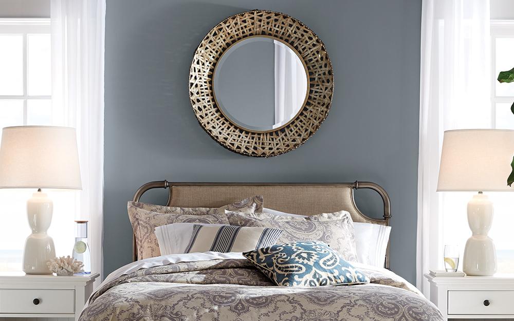 một chiếc gương tròn treo tường phía trên chiếc giường đã làm sẵn