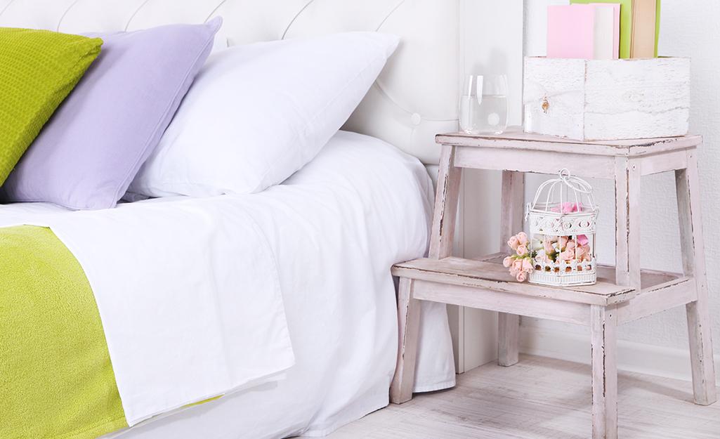 Bậc thang nhỏ sơn trắng dùng làm tủ đầu giường.