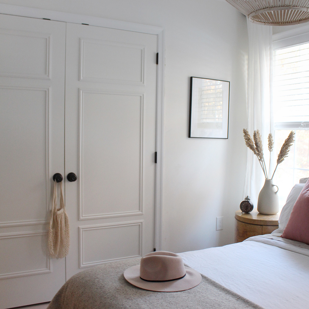 A bedroom with white closet doors and dark hardware.