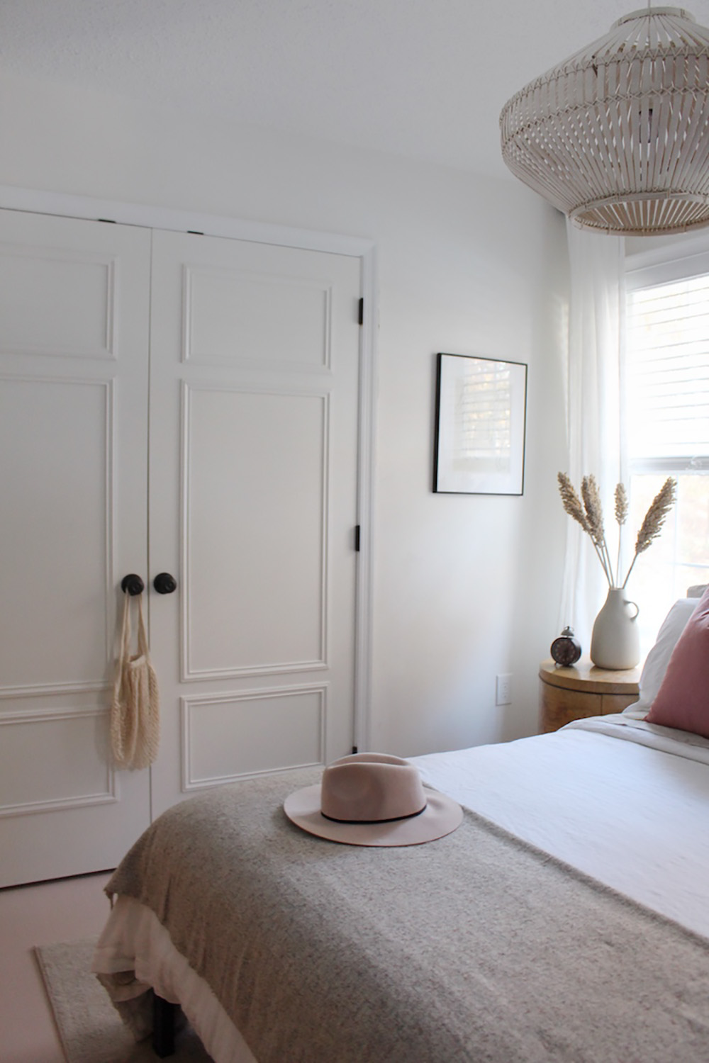 A hats sitting on the end of a bed with a large light above it.