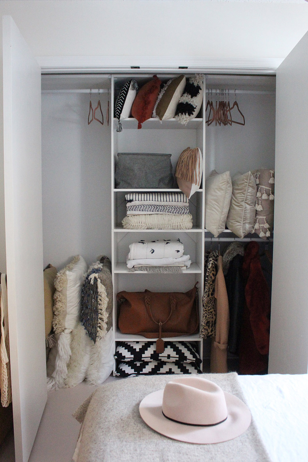 An organized closet with wooden shelving.