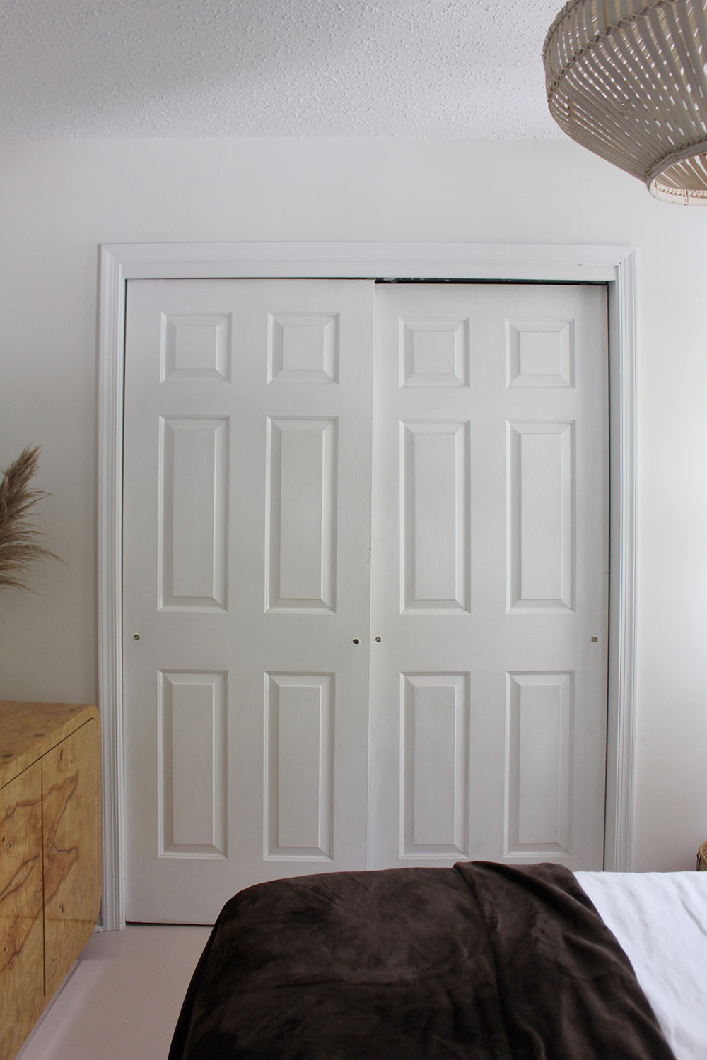 A closet with two six panel sliding doors.