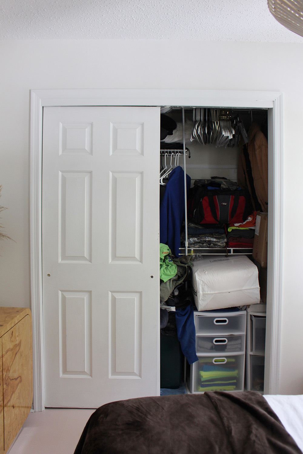 A closet with one door slid open filled to the top.