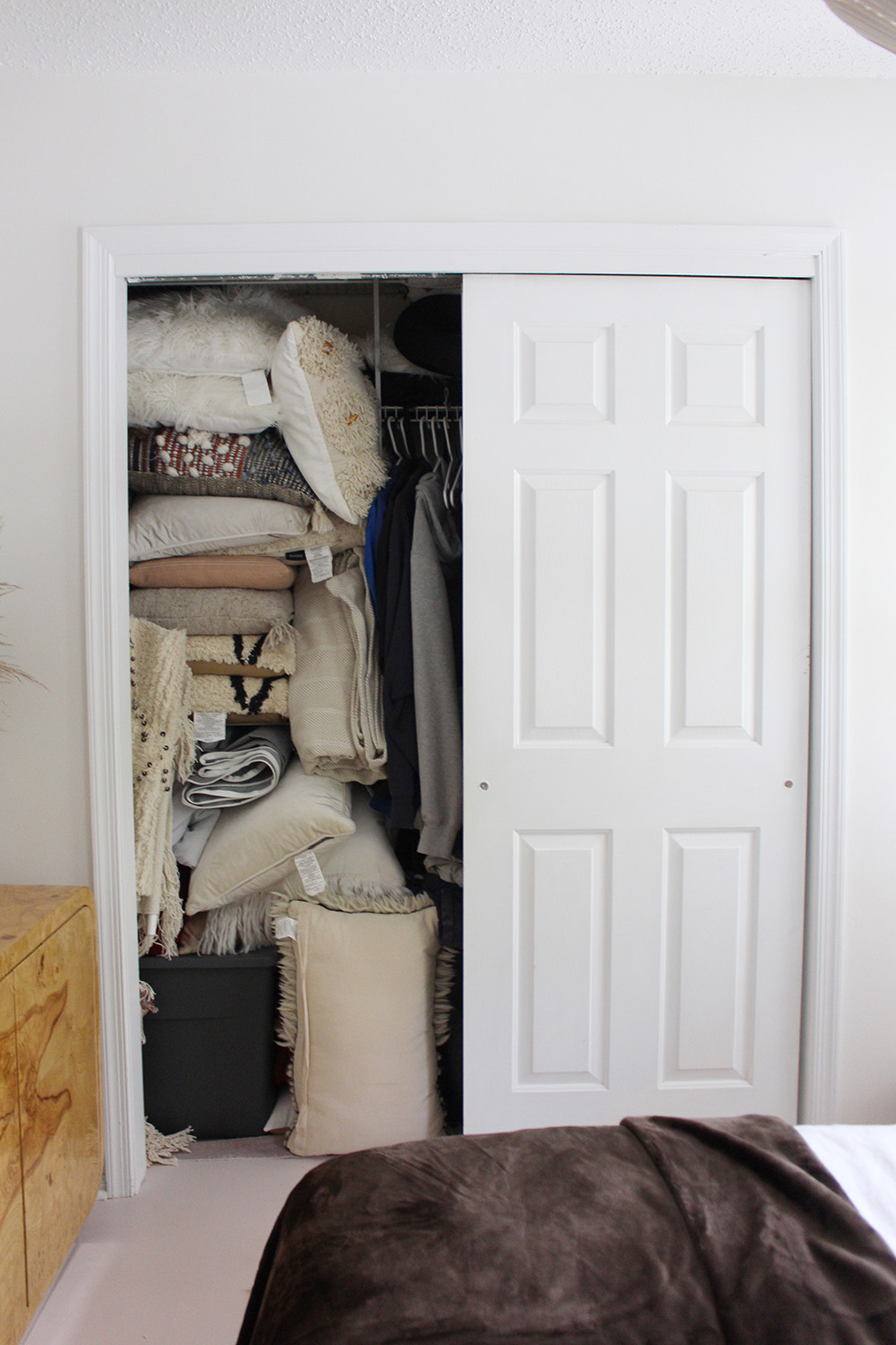 A closet with the other door slid open filled with pillows and linens.