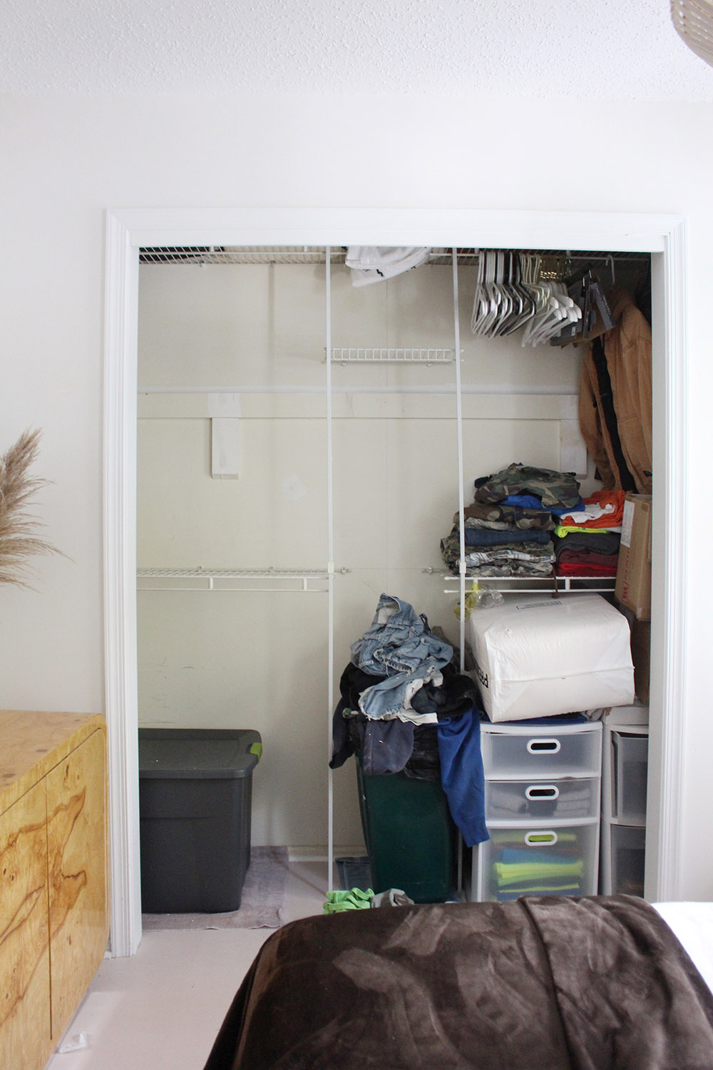 A partially cleaned out closet without doors.