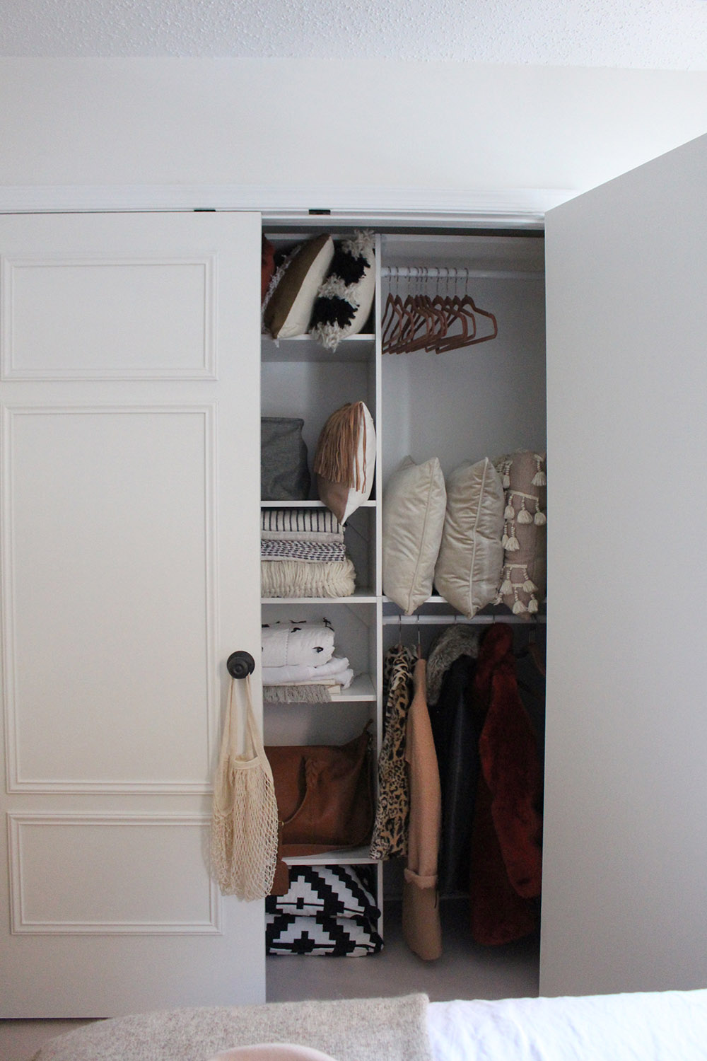 A closet with one door open shows organized wooden shelving.